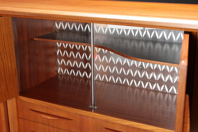 Danish modern teak sideboard by Danish furniture manufacturer. Sliding doors, drawers, and opening doors, with etched pattern mirrored glass inside.