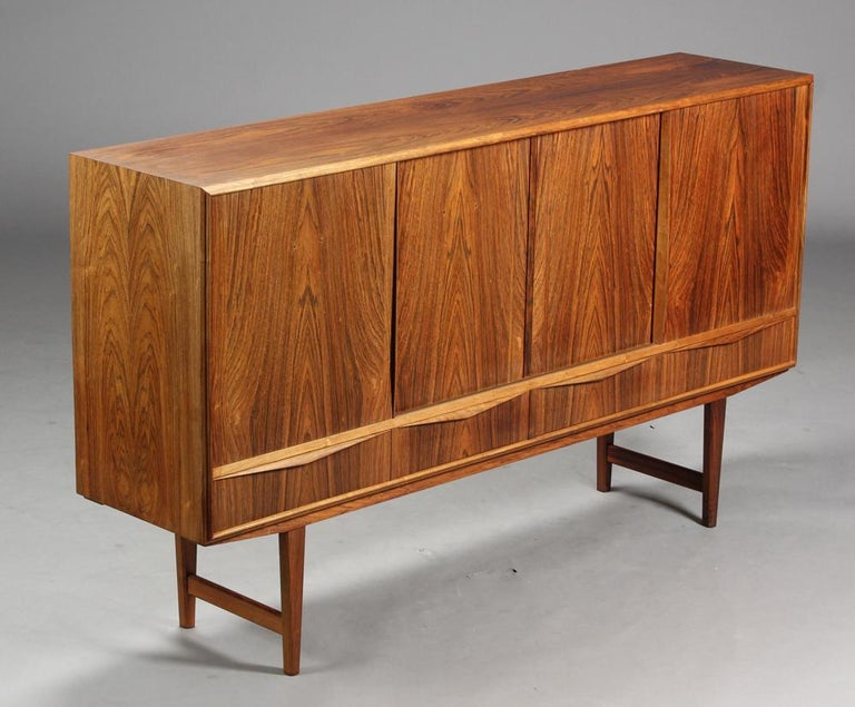 High rosewood sideboard by EW Bach. Front with sliding doors, behind which are shelves, drawers and mirrors. Manufactured by Sailing Cabinets, 1960.