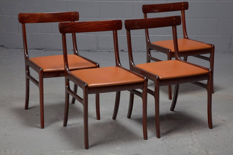 Designed by Ole Wanscher in the 1960s, this set of Rungstedlund dining chairs features a mahogany frame, a curved top rail for comfort, and a slightly reclined back. The seats are upholstered in cognac leather. Sold in set of four.