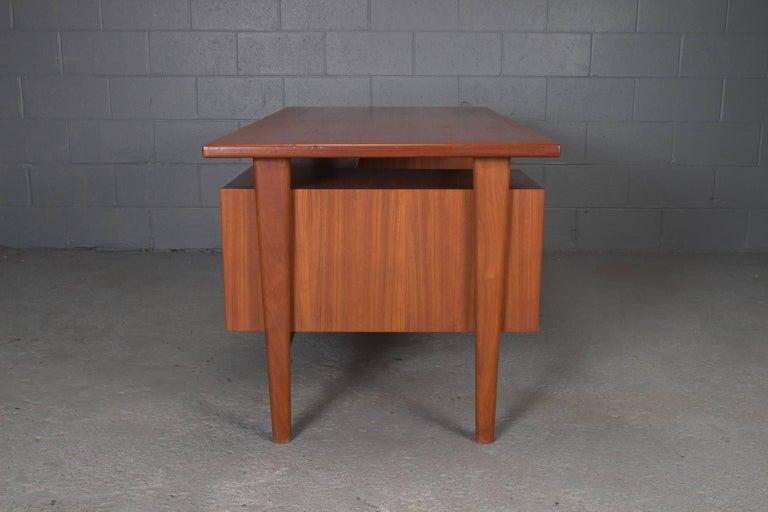 Danish teak desk with floating top by Kai Kristensen. Three open cubbies on opposite side.  This executive desk is Model FM 60 by Kai Kristiansen for Feldballes Møbelfabrik.