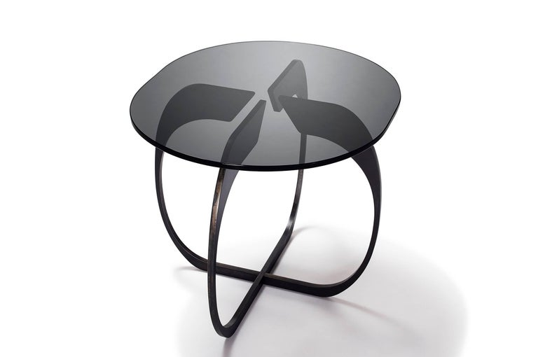 A smartly shaped side table that evokes the onion-inspired designs of the midcentury, along with modern updates. The table base is created with interlocking oval-shaped pieces of plate steel that fit together seamlessly. Glossy, thick-cut smoked