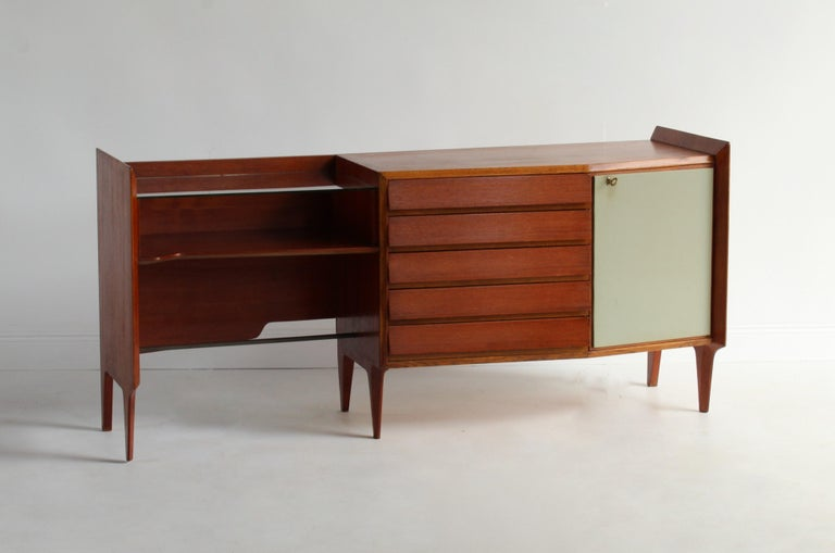 A rare, asymmetric modernist sideboard by Gio Ponti. Most likely produced by Dassi, Italy. in Mahogany and brass, with original glass, original light green vinyl, and original key. Sold with certificate of authenticity from Gio Ponti Archives.