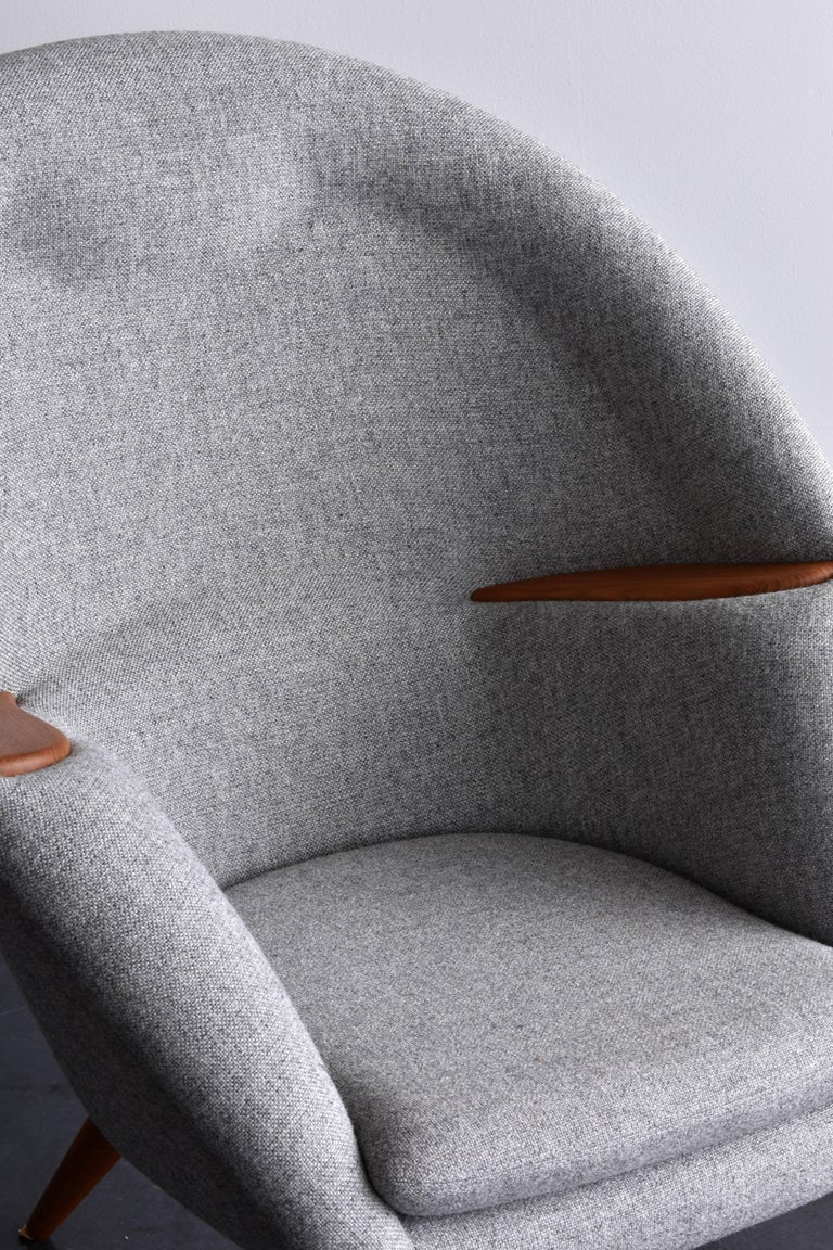A sculptural and comfortable lounge chair reupholstered in new fabric. Medium dark grey fabric provides an elegant contrast to the oak legs and armrests.  This early version was produced by Kolds Savværk in Kertminde, Denmark.  Other danish