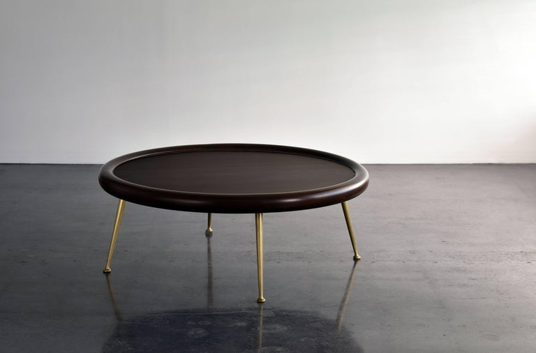 A modern coffee table partly lending it's aesthetics from ancient Grecian design. This theme being the hallmark of how the architect and furniture designerT.H. Robsjohn-Gibbings executed his designs.   The dark-stained walnut top provides a