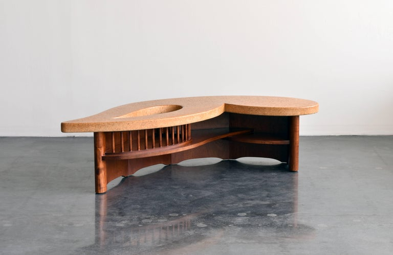 A very rare cork top coffee table or cocktail table by Paul Frankl for American manufacturer Johnson Furniture Company, circa 1955.  The playful cork top features a tear-drop shaped void, which sits atop a highly architectonic walnut base.  The form