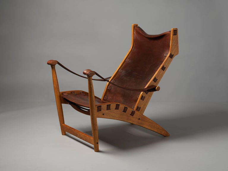 A Danish lounge chair in brown natural leather and oak, produced by Niels Vodder. The dark brown original aged saddle leather provides an elegant contrast to the patinated original oakwood. A fine example of Danish modern from one of the most
