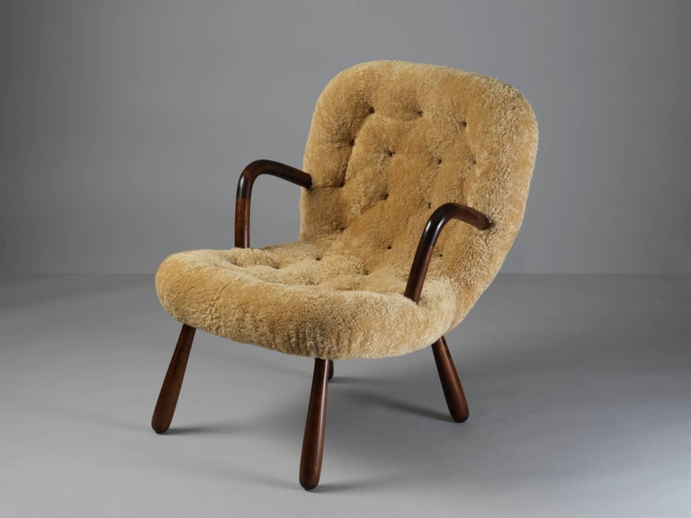An unusual organic lounge chair / clam chair, attributed to Philip Arctander. Dark stained beech frame, upholstered in natural beige sheepskin.  Philip Arctander had associations with Danish architects such as Flemming and Mogens Lassen and Arne