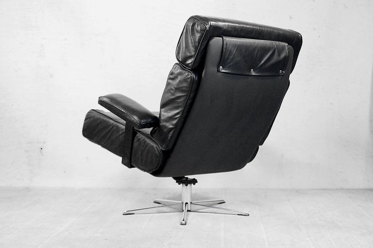 This office swivel armchair was manufactured in the Italy during the 1960s. The frame is made from metal. The chair is upholstered in real black soft leather, and the headrest has a leather slack overlap and is clasped on the back.