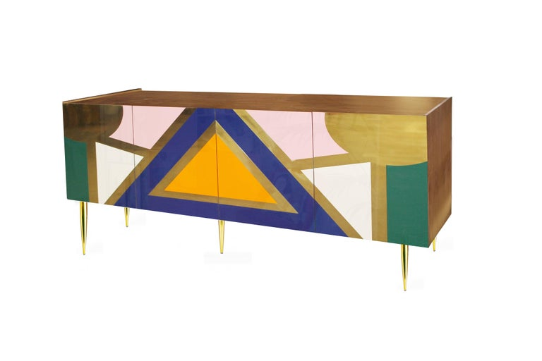 A tribute to colorful Mayan culture. The elemental shapes collide with dynamic results in this two double-door sideboard that rests on legs made from brass. It represents the union between design and craftsmanship through its unique