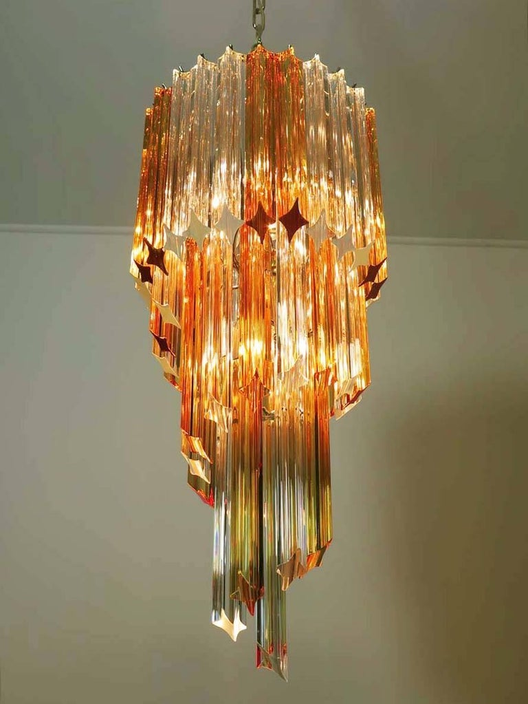 Pair of fantastic and big Murano chandeliers made by 54 Murano crystal prism (quadriedri) in a chrome metal frame. The shape of this chandelier is spiral. The glasses are of two different colors, 24 amber and 30 transparent.  Dimensions: 57.10