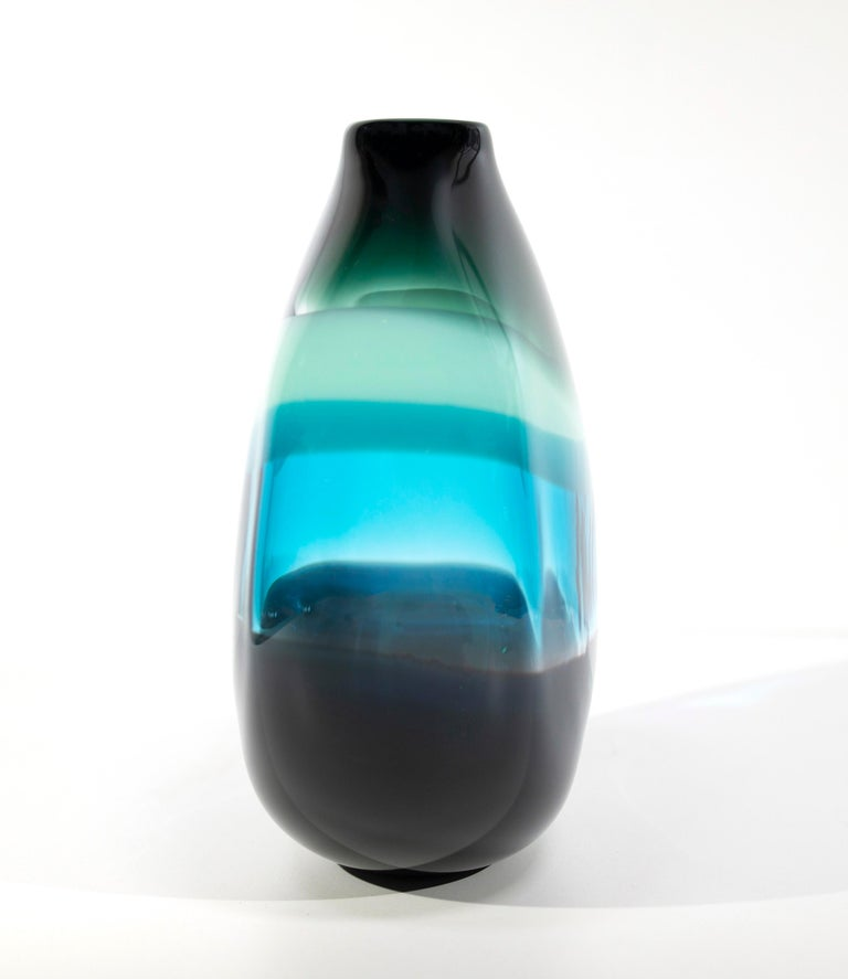 Aqua banded vase. Inspired by the rich hues and topography of Southern California, alternating layers of opaque and transparent colors are applied to clear glass. New colors are formed by overlaps, adding depth to the pieces. Simple shapes