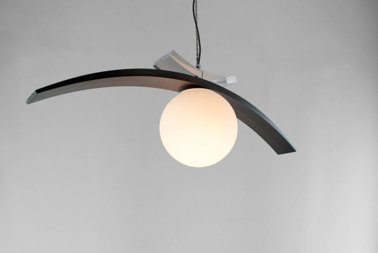 Louis Jobst' Eye Pendant is the abstracted form of an eye, hanging free in space. It is surreal yet contemporary creating an elegant and iconic design. The tapering maple eye lid provides many different shapes and forms due to its profile. The