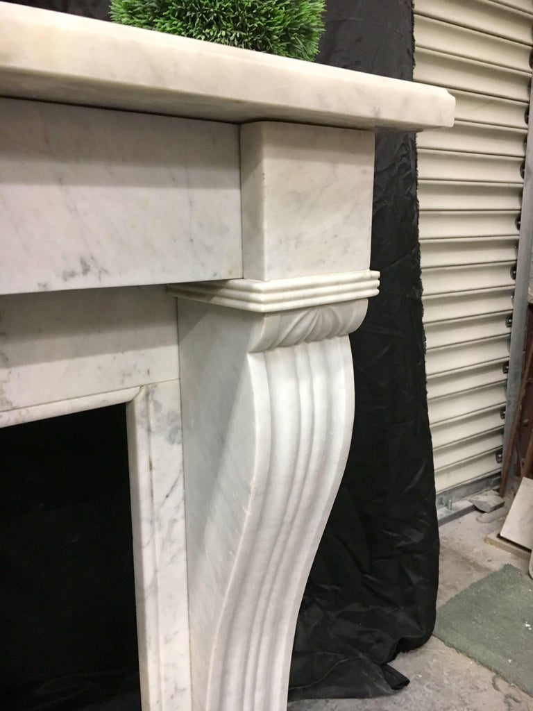 A fine and fully restored antique Carrara French marble fireplace with large sweeping corbels to legs.