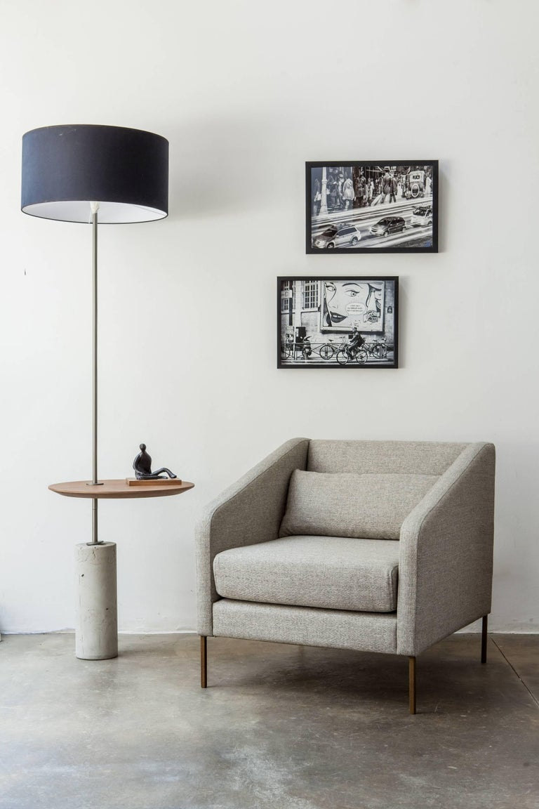 The Giro (Portuguese for spin) minimalist floor lamp fixture plays with the concept of movement and function. It presents a side table that spins around the stem fixed into a concrete base so it can be adjusted as needed. The designer Alessandra