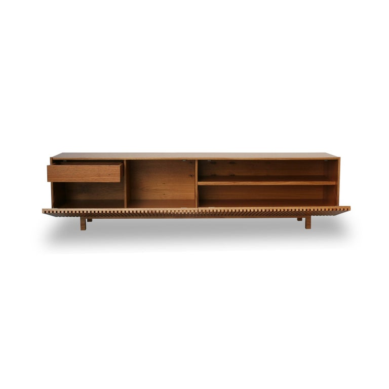 Inspired by the sun blocks or brises soleil featured on Modernist architecture which has captivated Alessandra Delgado since the early days of her career as a designer, Athena credenza design incorporates wood slat doors made using the finest
