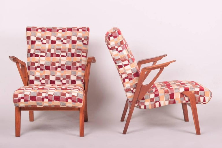 Pair of mid-century oak armchairs, it was made in Czechoslovakia in the 1960s. Design of these armchairs is inspired by the popular chairs of Italian designer Oswaldo Borsani. The armchairs are very comfortable. New upholstery including completely