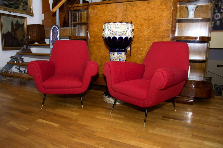 This pair of midcentury Italian lounge armchairs was designed by Gigi Radice for Minotti in the 1950s. The chairs feature new red upholstery and black-lacquered steel and brass legs.