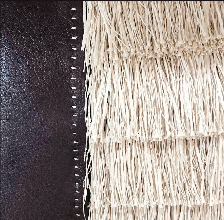 A fine  calf leather has been meticulously hand stitched to showcase the three inch raffia fringe. The hand stitching and the inset fringe create a truly couture pillow   Details •Fine calf leather •Hand stitching detail  •Includes down