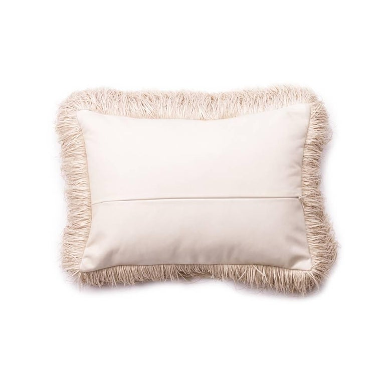 Antique kuba cloth with an inset cream leather hand stitched under the antique fabric. This pillow is finished with a 3 inch raffia fringe and a cream leather back. Made in Los Angeles and includes down insert.    Dimensions: 16 in x 11 in x 6