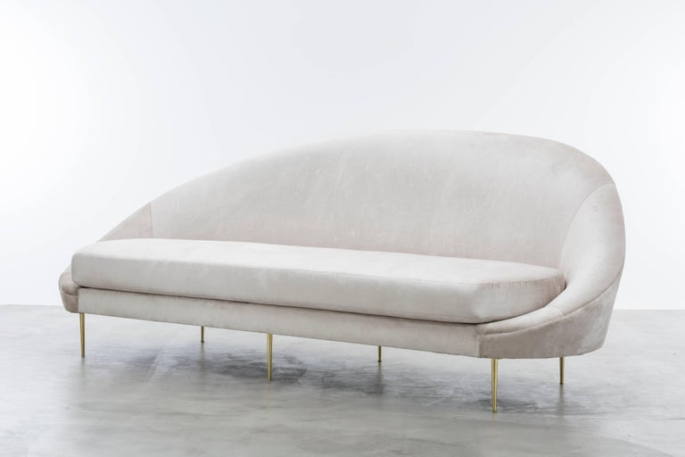 The Sandrine Sofa inspired by the curvature of Gaudi architecture features an asymmetrical sophisticated velvet slope that meet solid brass legs to make a minimal and elegant statement.  Fully custom and made to order in California.  As shown in