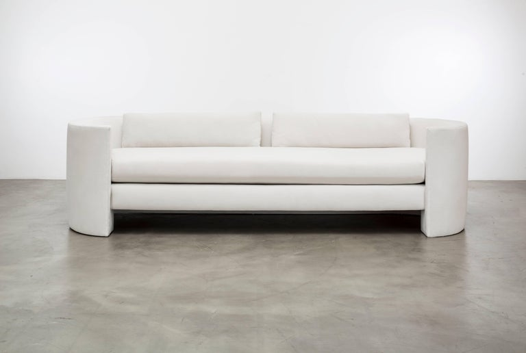 The Claire sofa features an upholstered hovering plinth cushion seat and a back waterfalls to the floor. This is a showroom sample sold as is. As shown in a cotton velvet white.