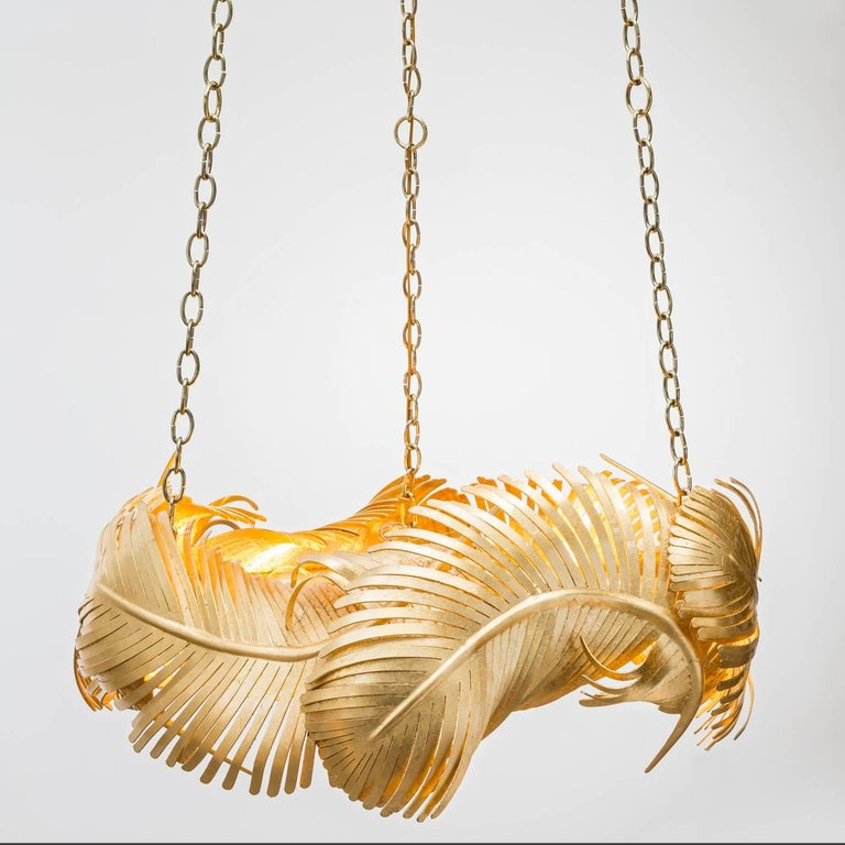 The Josette chandelier is a sculptural fete featuring hand-forged gold leaf over iron feathers suspending from custom brass poles. Light bulbs: Eight clear globe g25 standard base 60 watt max (not included). This is a showroom sample sold as is. CSA