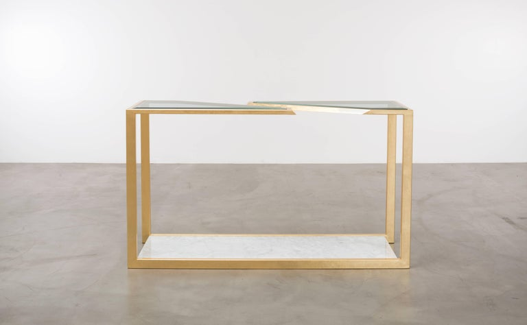 The Pierre console table is a modern fractured gold leaf console table made of gold leaf over iron with Carrara marble and bevelled edge glass. This is a showroom sample sold as is.