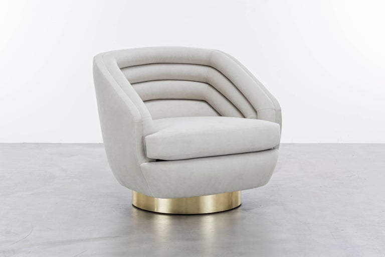 The Raoul Chair inspired by Jean Paul Gaultier Haute Couture features horizontal velvet channels on a brushed brass swivel plinth base.  Fully custom and made to order in California. As shown in Ultra Suede $9,160. Starting at $7,410.
