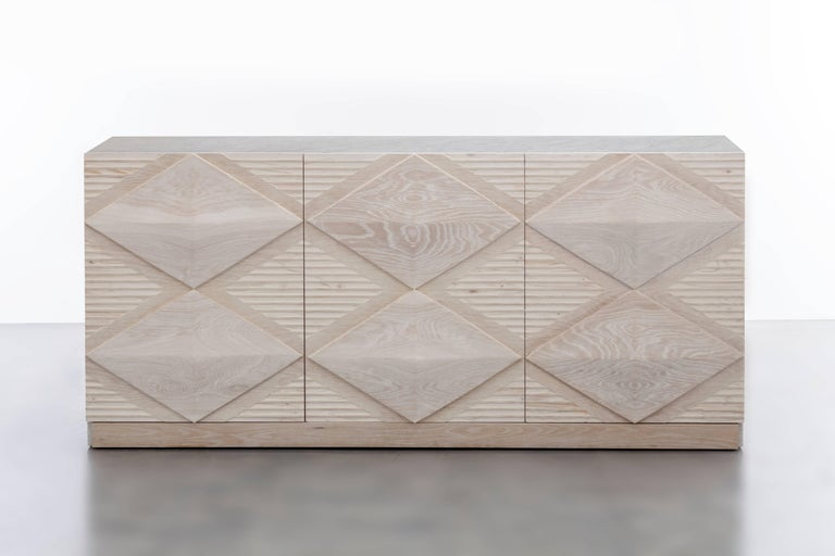 The Ines Buffet Cabinet features a bleached white oak body with hand carved oak diamond details and a waterfall cararra marble top. The interior standard comes standard with adjustable shelves and can be customized to any interior needed whether it