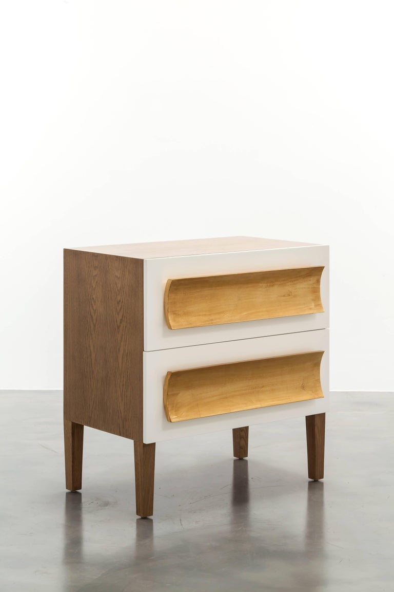 The Recaimer nightstand features a unique mixed finish design with an oak body, lacquer drawer fronts and gold leaf hand-carved pull details. Drawers are standard soft close with hidden glides. Fully custom and made to order in California.
