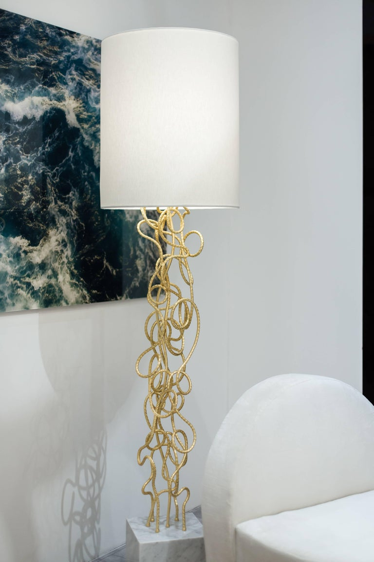 The Dax floorlamp is a sculptural fete featuring gold leafed rebar hand twisted to create a unique one of a kind statement. Polished brass, Carrara marble and a white linen shade finish this piece off. Light bulbs: One standard medium base 60 watt