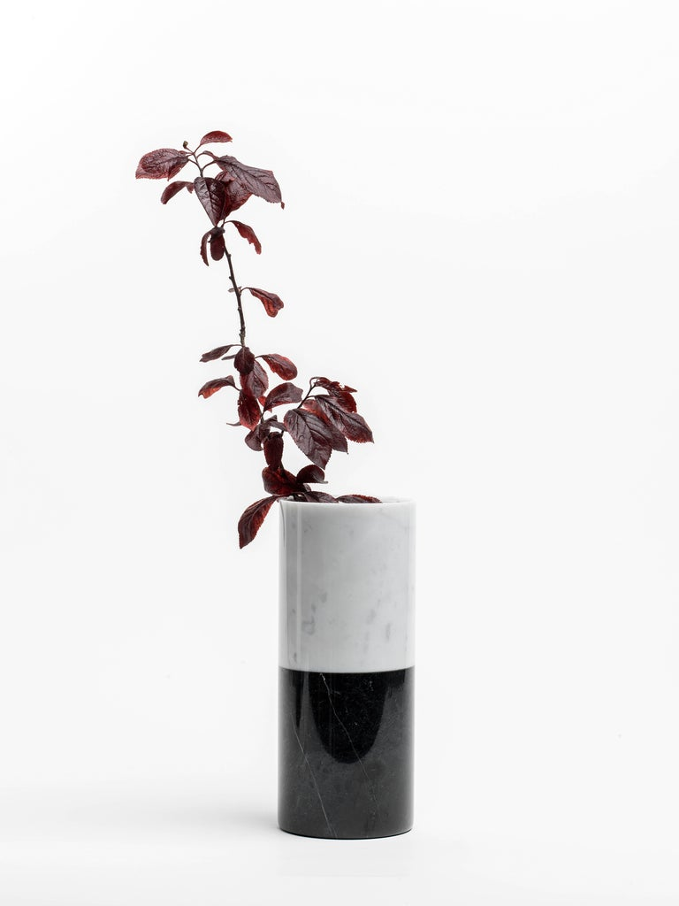 Cylindrical white Carrara marble vase with bottom black band, made in Italy, Carrara. Each piece is in a way unique (since each marble block is different in veins and shades) and handcrafted in Italy. Slight variations in shape, color and size are