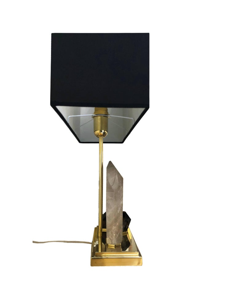 Stunning midcentury style table lamp in polished brass and quartz stones. On the rectangular base are nestled three quartz, the larger in fumè with beautiful brown shades and the smaller two in smoked dark grey color. Each lamp is unique in its