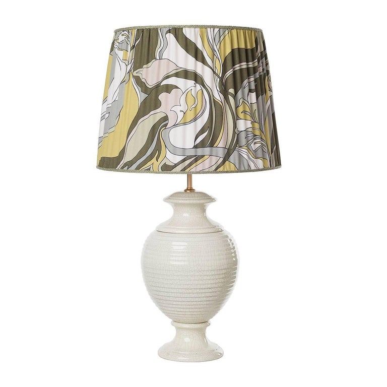 Pair of striped table lamps and shades. The items feature a classical sinuous shape enriched by a crackled ivory glazed surface and completed by a cylindrical pleated shade in a fancy pattern fabric. Wired to your request, 1 x E27/E26 screw bulb.