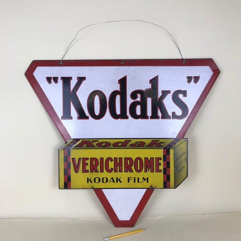 This very beautiful double-sided triangular multi-colore metal enamel Kodaks sign was produced in France, circa1940s by Japy. The Kodaks logo is placed on a white and red background over a 3D film box image