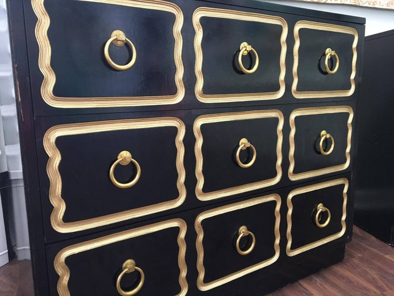 Pair of matching Dorothy Draper style Espana dressers in the iconic black with gold trim. Features brass hardware and dovetail jointed drawers. Good vintage condition consistent with age.