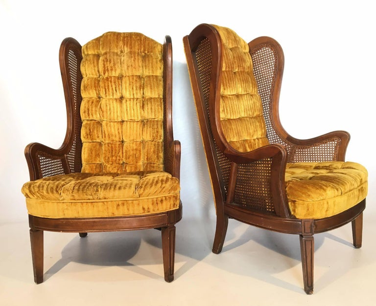 Pair of Lewittes cane wingback chairs in gold velvet. Features full tufting from back to seat. Caning in near perfect condition. Upholstery in excellent condition and frame also in excellent condition, save for the slight wear on
