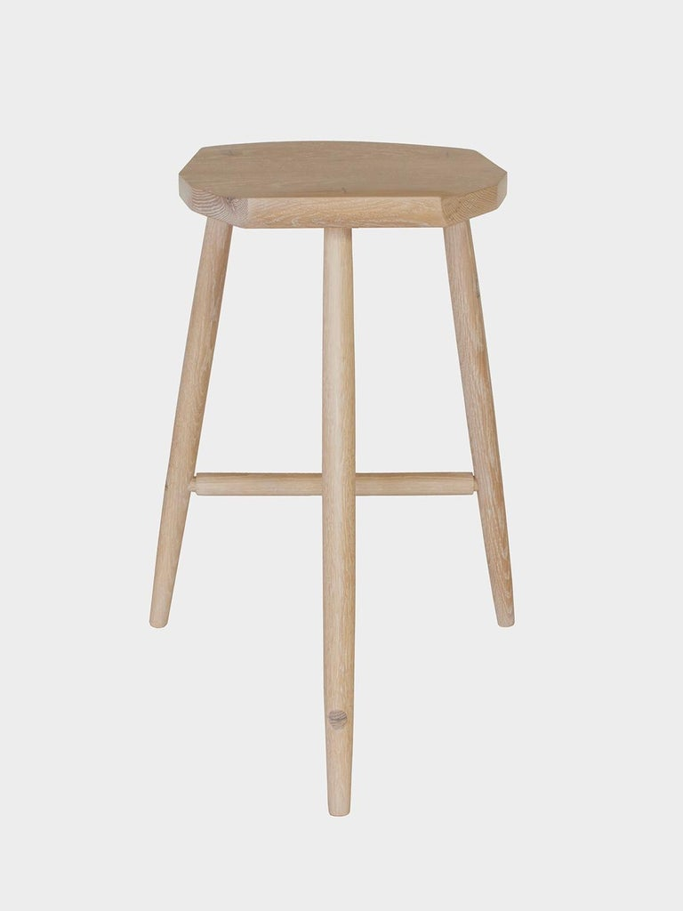New York Heartwood's counter height cerused white oak solid wood Hudson stool is designed for comfort and stability and features three hand-turned legs, a shaped faceted seat, and walnut wedged tenons.  Each is made with wood milled from fallen