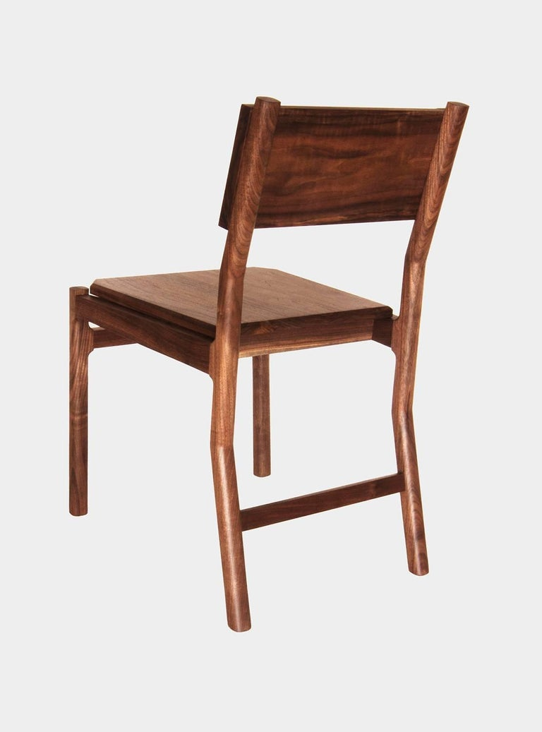 New York Heartwoods' contemporary black walnut Hewitt dining chair is influenced by Mid-century Modern and Shaker design, designed for comfort, and features refined joinery, a hand-shaped backrest, a faceted seat, and NYH's signature teardrop post