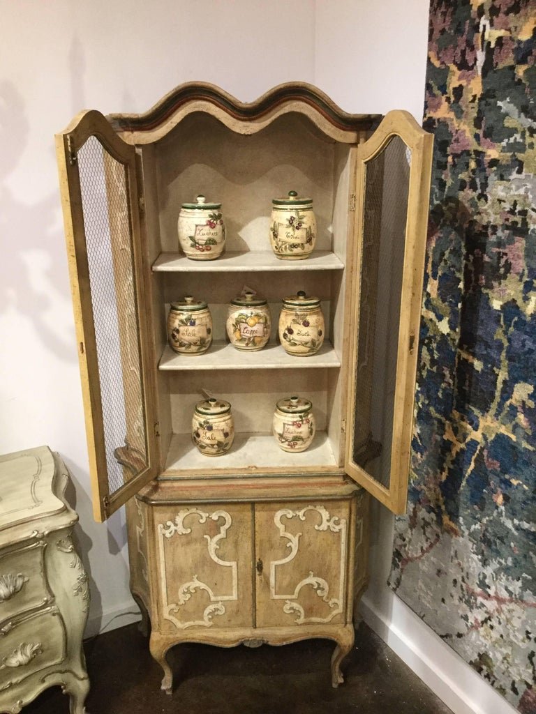 Hand-painted tall cabinet featuring distressed ochre finish with cream, red and green accents, two upper doors with chicken's netting and two lower doors.  Created by the artisans of Italy.