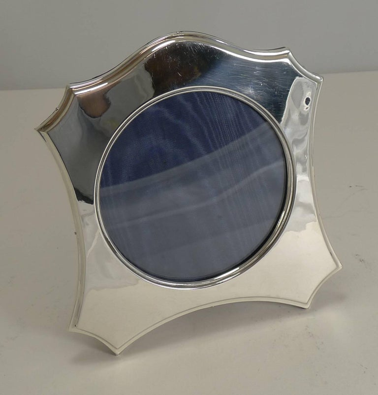 A very elegant English sterling silver photograph frame, beautifully shaped with a central circular glazed aperture.  The backing is made from solid English oak incorporating a hinged folding easel stand.  The silver is fully hallmarked for