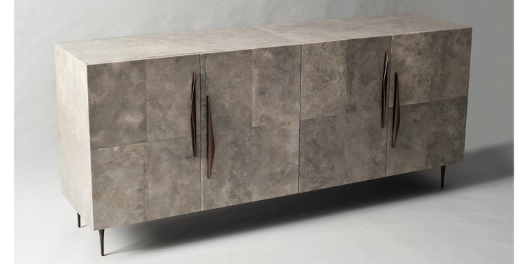 The Antwerp cabinet or credenza by DeMuro Das is sheathed in matte grey Carta, a unique material similar in appearance and application to parchment. The curved handles and delicately tapered legs are made from solid antique bronze.