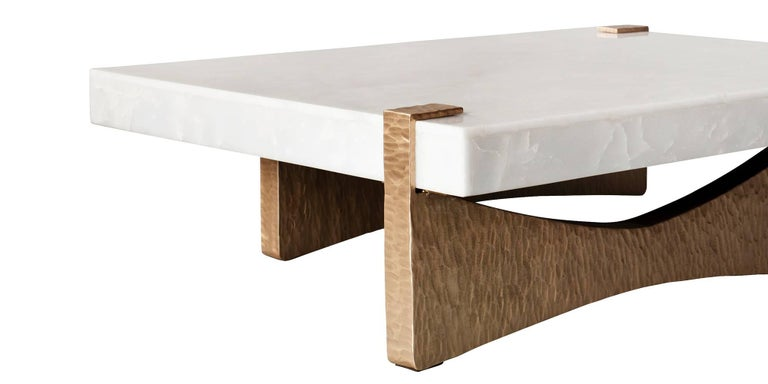 The Moore coffee or cocktail table by DeMuro Das has a stone top in White Onyx, supported by a hand-cast sculptural base in a beaten Bronze finish. This is a substantial piece with a great deal of presence.
