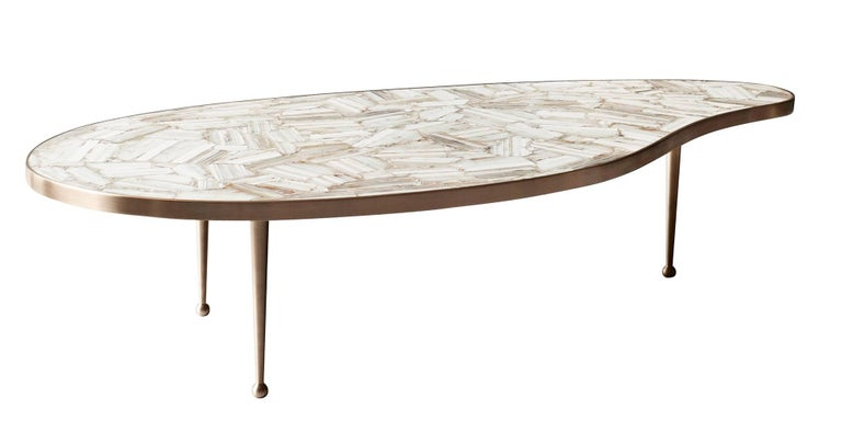 The bio-morphic shape and clean lines of the Lola coffee table by DeMuro Das were inspired by midcentury design. With a stone top made of polished, hand-laid creamy white agate, the table surface is both luxurious and functional. Hand-cast, solid