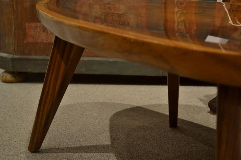 These 1960's pieces have cross cut tops of exotic timbers. The legs are gracefully tapered, with the coffee table having four legs, and the side tables three. They have their original finish with some scuffing. The dimensions of the coffee table are