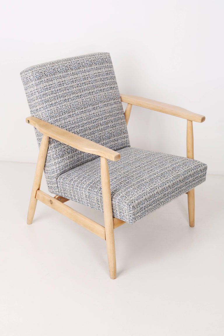 A very comfortable, stabile chair designed in the 1960s. It was made in Poland. The chair is after full upholstery and carpentry renovation. The seat is covered with high quality fabric with a small pattern.