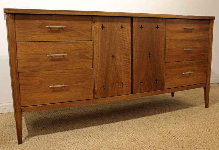 Offered is a Mid-Century Modern sculpted walnut credenza. This piece is from the
