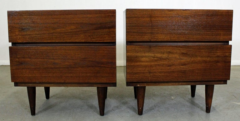Offered is a pair of walnut nightstands made by American of Martinsville. Feature two drawers with hidden pulls. They are in good condition; tops and sides have been refinished. They are signed by American of Martinsville.  Dimensions: 22
