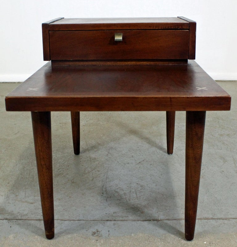 Offered is a walnut end table designed by Merton L. Gershun for American of Martinsville. Features one drawer with a brass pull and the iconic x-shaped brushed aluminum inlaid detailing in the tabletop. It is in very good condition, shows some