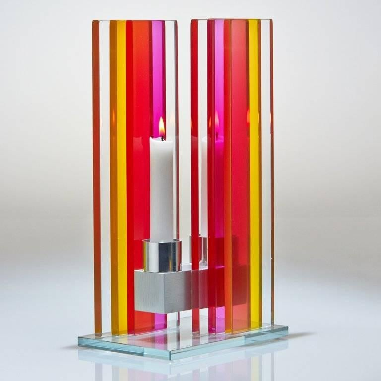 This polished glass, double candleholder is designed by world renowned glass artist, Sidney Hutter. With 40 years of experience in the contemporary glass and fine art world, Sidney now creates illuminated designs for the home. Create a centrepiece